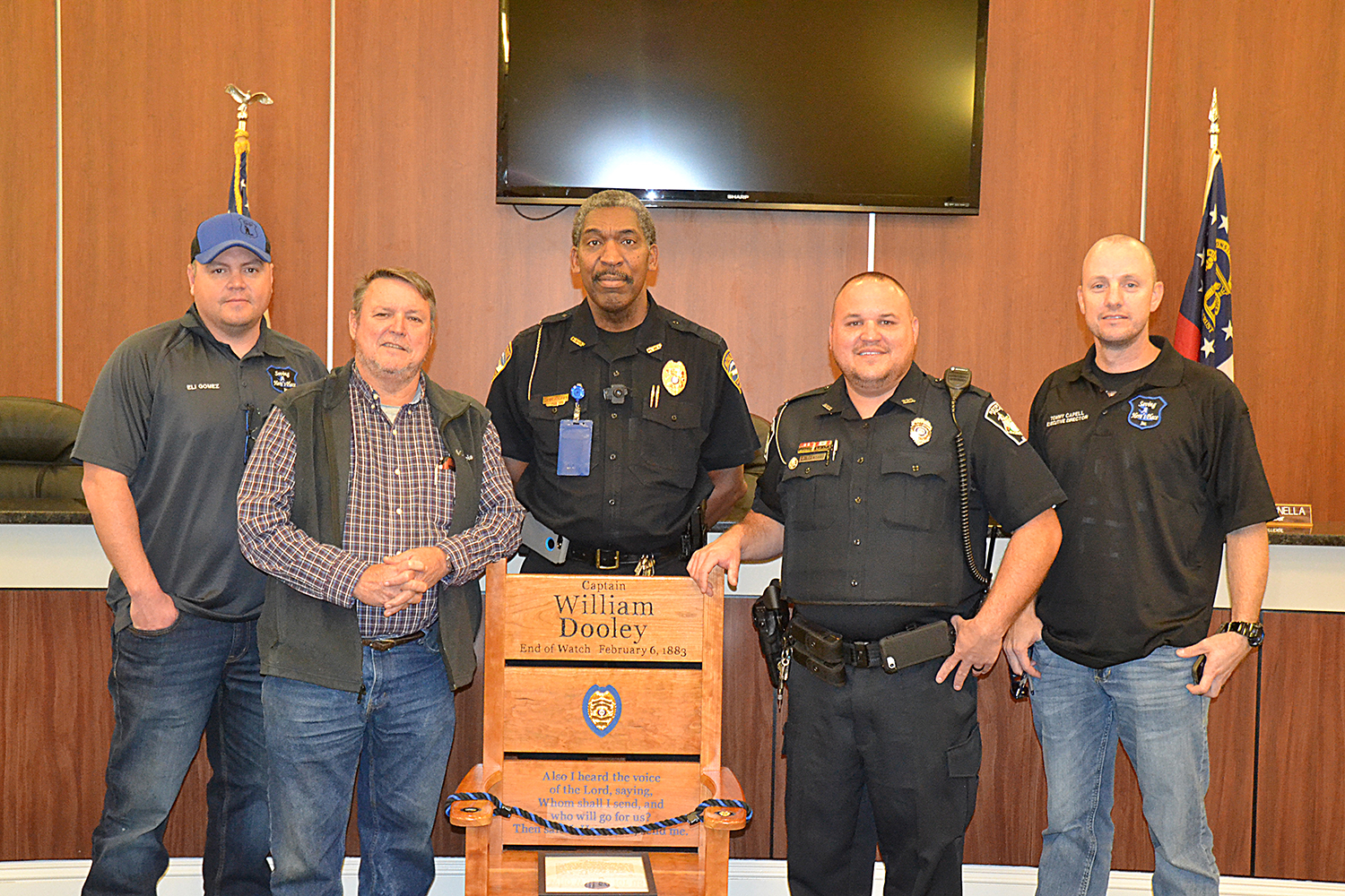 Sunshot by Drew Dotson — Eli Gomez, from left, Hart County Commissioner Ricky Carter, Hartwell Police Chief Anthony Davis, Royston police officer Rick Carter and Tony Capell pose for a photo with a chair donated by Gomez and Capell's nonprofit, Saving a Hero's Place.