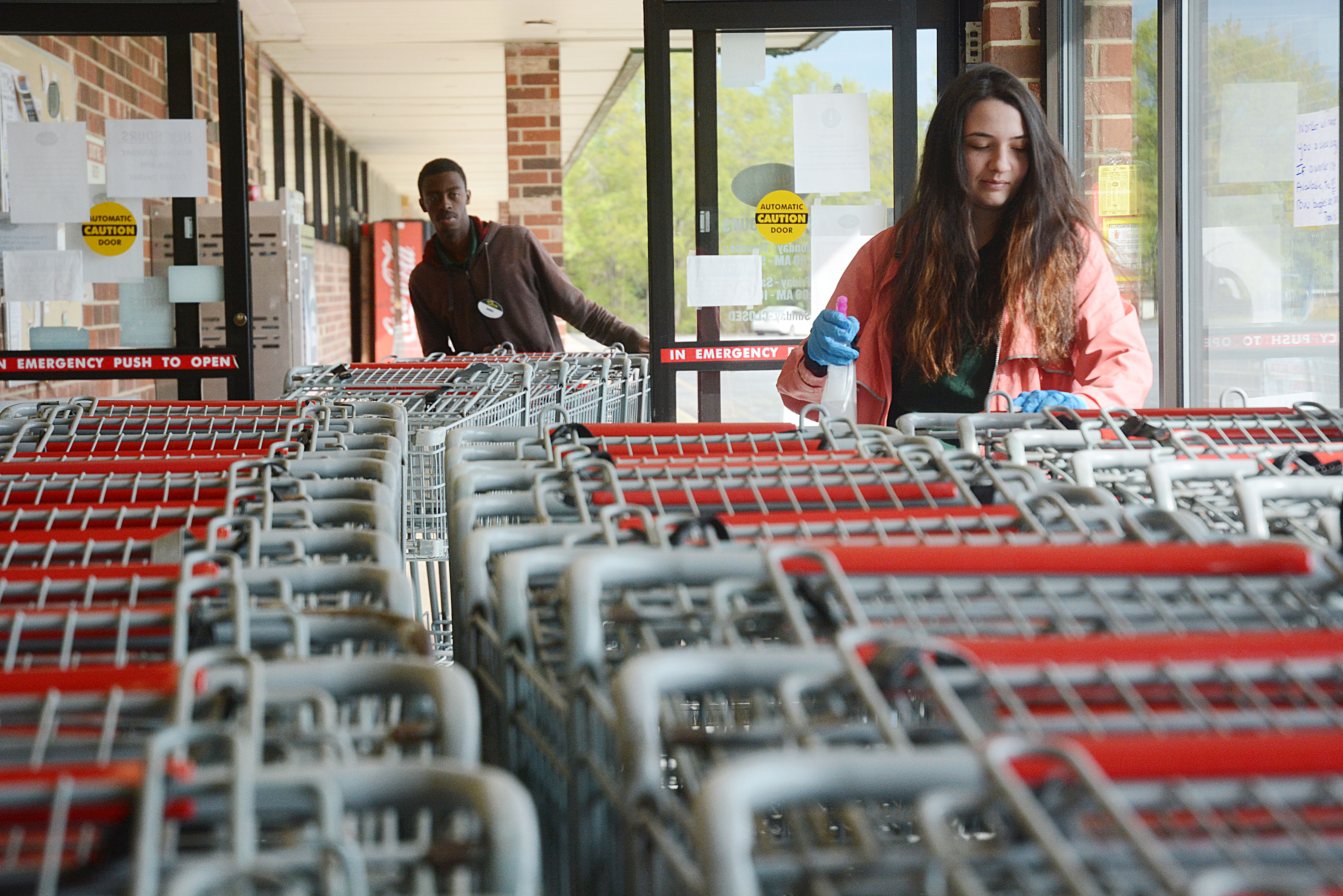 Sunshot by Michael Hall -- Darius Hunt, left, brings in carts from the parking lot at Quality Foods in Hartwell on Tuesday, March 31, as Kelsie Dean, right, cleans them to disinfect them as part of the store's response to the COVID-19 pandemic.