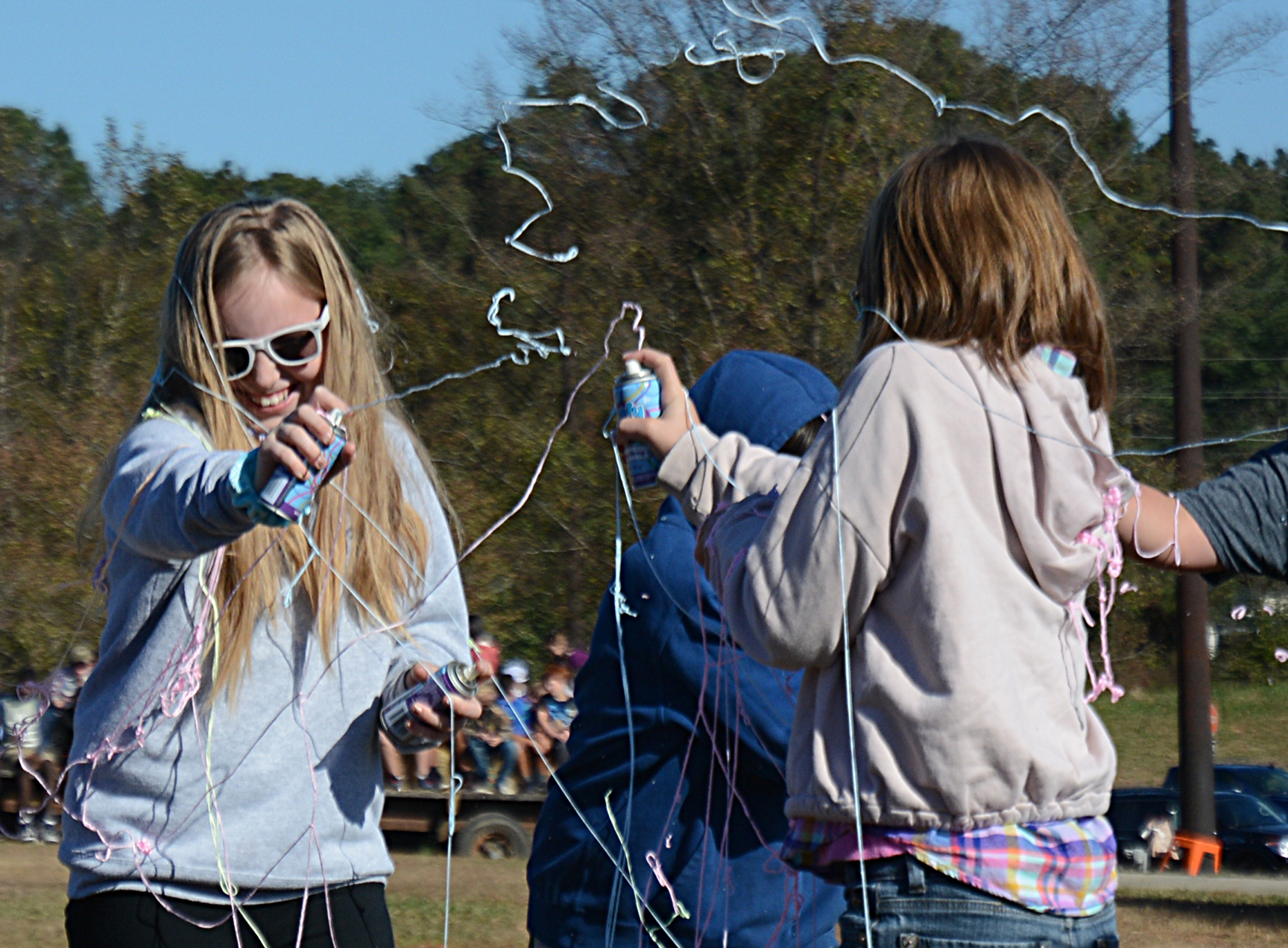 Brooklyn Vassar, left, and Mia Dancause, right, both fifth-graders, duel with cans of silly string during the Silly String Club Day activity.