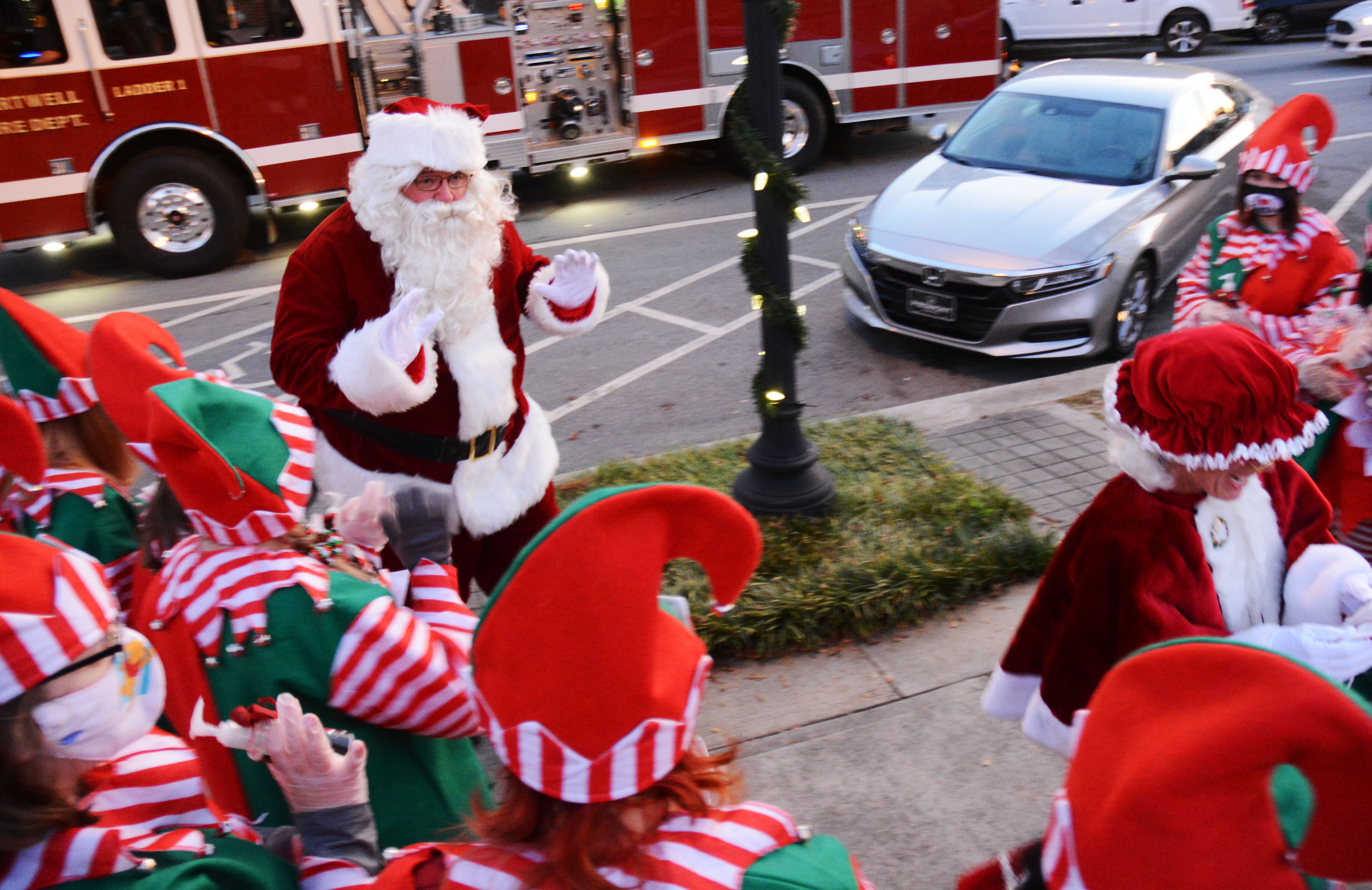 Santa waves to his elves as they greet him and Mrs. Claus, who hitched a ride to the event with the Hartwell Fire Department.