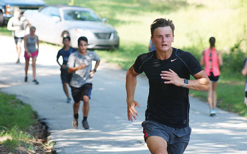 Sunshot by Grayson Williams — AJ Johnson runs up a hill recently at Hart County High School cross country practice.