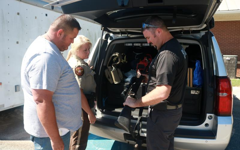 Sunshot by Grayson Williams -- Hart County Sheriff's Office investigators Kevin White, Kristi Hughes and Chris Carroll look at equipment recently at the Sheriff's office.