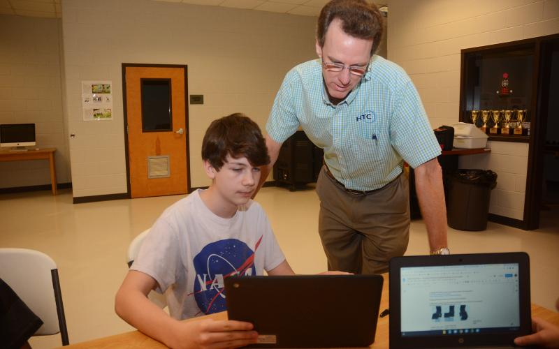 Sunshot by Michael Hall — Seventh-grader Wyatt Zimmerman, left, shows HTC president Randy Daniel his work recently at Hart County Middle School. HTC is a regular supporter of the Hart County Charter System.