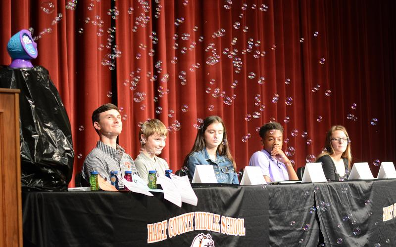 Sunshot by Michael Hall — The 2019 class of REACH Scholars, from left to right, Mason Carey, Ethan Cleveland, Emily Evans, Jashon Gaines and Trinity Wilson, watch bubbles fly as keynote speaker Dink NeSmith, Community Newspapers Inc. president, makes a point about dreams needing to be protected like soap bubbles floating in the wind past jagged rocks.