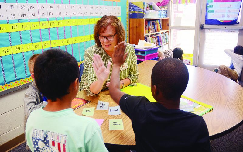 Sunshot by Michael Hall — Jenny Martin high-fives a second-grade student after he successfully identified a word in a reading exercise recently at Hartwell Elementary School.
