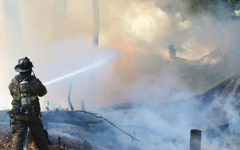 Sunshot by Grayson Williams — Hart County Firefighter Teddy Gibson douses the flames of a fire that burned a vacant mobile home on Whippoorwill Trail on Sept. 25.