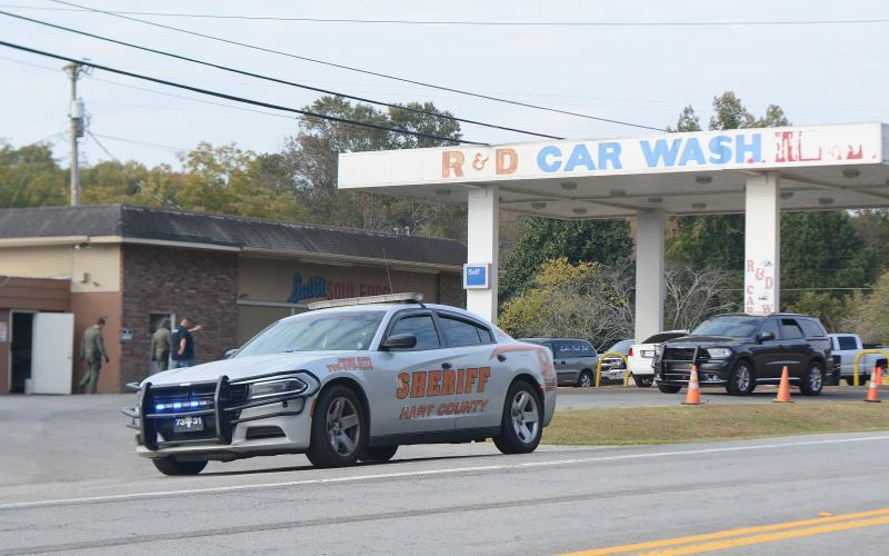 A Hart County deputy's car is parked at the entrance of R&D Car Wash on Anderson Highway as the GBI and other authorities investigate an alleged racketeering scheme they believe involves Hart County commissioner R.C. Oglesby.