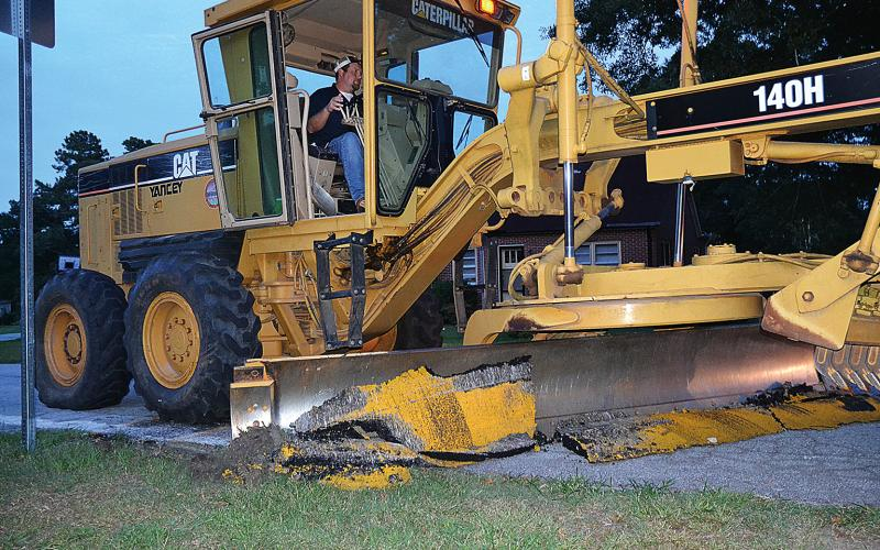 A Hart County road crew employee removes the speed bumps in Bowersville in August.