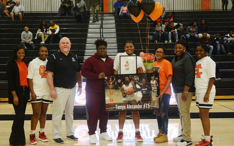 Sunshot by Michael Hall — Taniya Alexander, center, holds a poster and other items given to her to honor her for scoring 1,000 points for Hart County. Pictured are coach Joreshica Martin, Tanyzia Teasley, head coach Mike Edwards, Demardric Thornton, Alexander, her mother Tammy Scott, coach Dannette Bowers-Davis and Shakendra Grove.