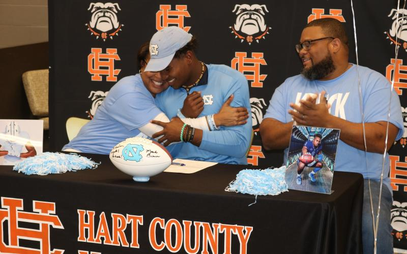 Sunshot by Grayson Williams — Kristi Rucker, left, hugs her son Kaimon Rucker, center, as his father, Kendall Rucker claps during Kaimon's signing day ceremony on Dec. 18. Kaimon will play college football at the UNiversity of North Carolina.