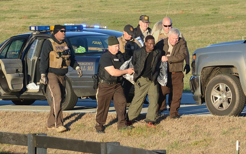Sunshot by Michael Hall - Hart County Sheriff Mike Cleveland, right, and deputies escort Larrendrick Rashad Tabor, center, from a squad car to an ambulance after his arrest Tuesday, Jan. 28, for his alleged involvement in a Monday night murder in Hart County.