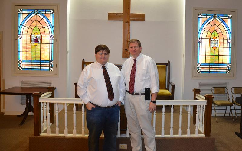 Sunshot by Drew Dotson - Matthew Strickland, left, and Arnold Strickland, right, pose for a photo in the chapel at Strickland Funeral Home in Hartwell. The funeral home is turning 45-years-old this year.