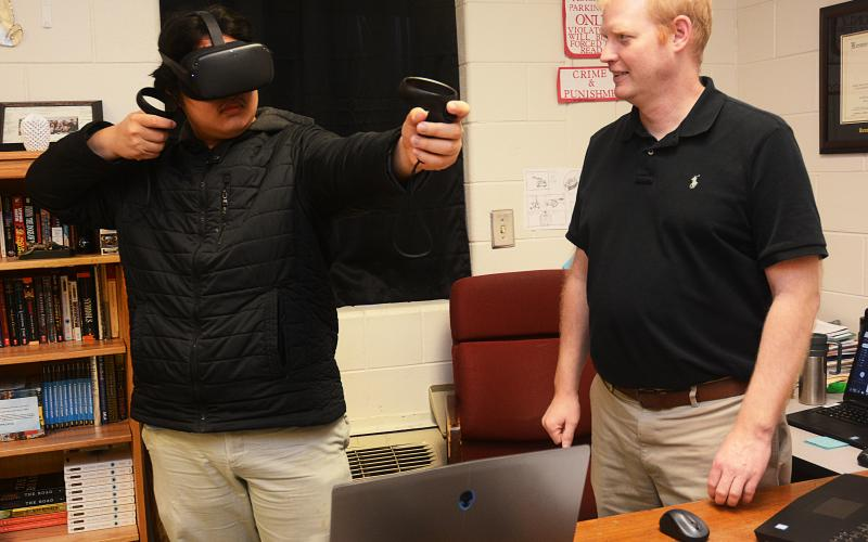 Sunshot by Michael Hall — Hart County High School's STAR student, Sean Pak, left, and STAR teacher, Rob Elliot, right, demonstrate a virtual reality game in February that they had hands in creating. It is one of many stories from the Hart County Charter System covered by The Sun.