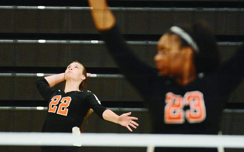 Sunshot by Michael Hall - Madison Wolfe serves during the Hart County Volleyball team's win over Rabun County on Aug. 20 as LaMaya Sessoms prepares for action.