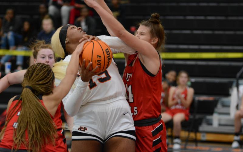 "Sunshot by Grayson Williams - Taniya ""Nesha"" Alexander tries to power through Loganville defenders on Monday at Hart County High School during the McDonald's Shootout. The Hart County Lady Dogs fell by one point on Tuesday in the semifinal game."