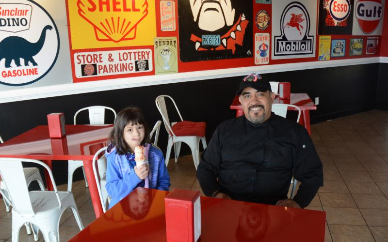 Omar Vega, right, and his daughter, Anna Blazek, left, sit in the newly remodeled Scoops by Rolling Chefs.
