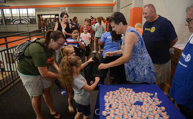 Hartwell Rotary Club member Ganine Derleth gives hand sanitizer to Elektra Head, 7, and her sister Ziva Head, 5, while their mother Kimberly Head helps and club member Mike Everett, standing at right, looks on.