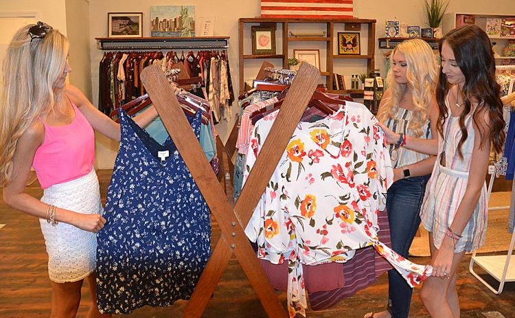 Empire South employees Autumn Gretsch, Megan Crump and Savannah Hackett go through a selection of current styles at the store.