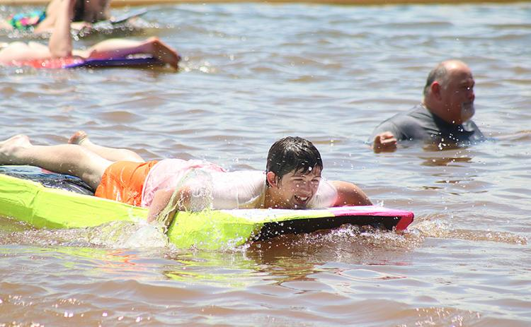 Sunshots by Grayson Williams — Carter Reed navigates his paddle-board style boat past band director Alan Tolbert, right, who officiated the event from the water.