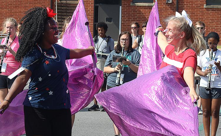 Flag corps members Detricunna Teasley, left, and Samantha Campbell, right, practice their flag routine during Hart County High School band camp on Monday.