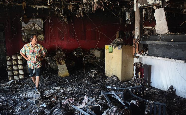 Sunshots by Michael Hall Little Japan co-owner Tommy Vang walks through the dining room and past the sushi bar at the restaurant on Tuesday as insurance adjusters assess the damages from an Aug. 9 fire.