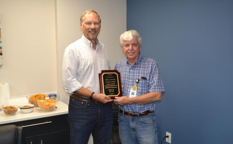 Terry Norton, right, retired this week after 50 years of service to Royston LLC. Norton was presented with a plaque commemorating his five decades of hard work by engineering manager Ben Credle, left.