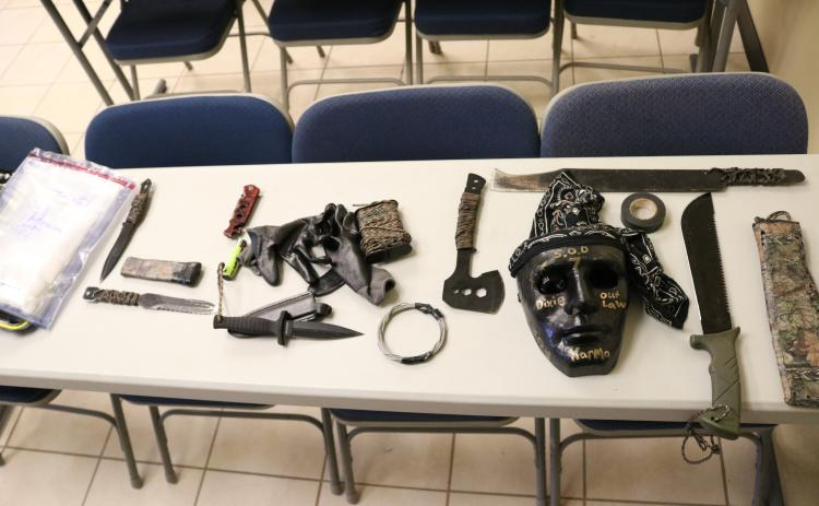 A bag of methamphetamine, at left, allegedly taken from a Hart County man, and knives, a hatchet, machetes, a mask and other items, allegedly taken from people out to kidnap and kill the man, are shown.
