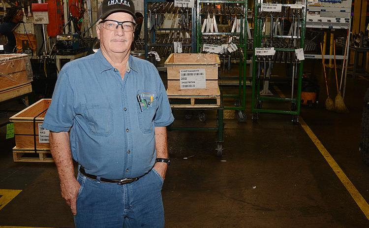 Sunshot by Michael Hall — George Adams poses for a photo in the factory at Tenneco where he has worked since 1959. He will retire when the plant closes later this year.