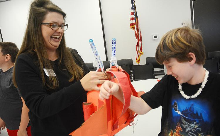 Sunshot by Michael Hall — North Hart Elementary School Teacher of the Year Emilee Patrick helps Ryan Belanger put a jetpack he invented on his back during the recent Invention Convention at the Agriscience Center.