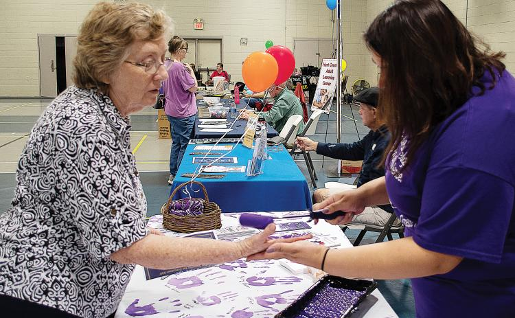 Sunshot by Karen Sokol — Carolyn Mullenix, left, has her hand painted purple by Isabel Bocanegra, right, to take the Purple Pledge with the Northeast Georgia Council on Domestic Violence for Domestic Awareness Month at the Hartwell Helps EXPO on Oct. 5.