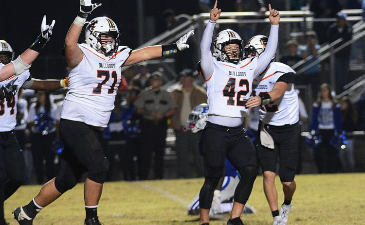 Sunshot by Michael Hall - Hart County kicker Tucker Kim, No. 42, raises his hands in victory along with Caden Hart, No. 71, while quarterback Luke Lee tackles Kim after Kim's game winning field goal on Nov. 22 in Blackshear over the Pierce County Bears.