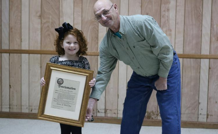 Sunshot by Grayson Williams - Outgoing Bowersville Mayor Jim Jordan, right, poses for a photo with Lainey Moon. Jordan proclaimed Aug. 25 as Lainey Jo Moon Day at a meeting on Dec. 19 after Moon won a Cabbage Patch Doll look-alike contest.