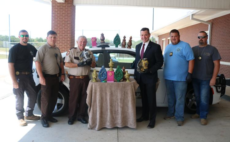 Sunshot from file — Hart County Sheriff Mike Cleveland, to the left of the table, and District Attorney Parks White, to the right of the table, pose for a photo earlier this year with deputies and a large amount of methamphetamine that had been formed in the shape of candles.