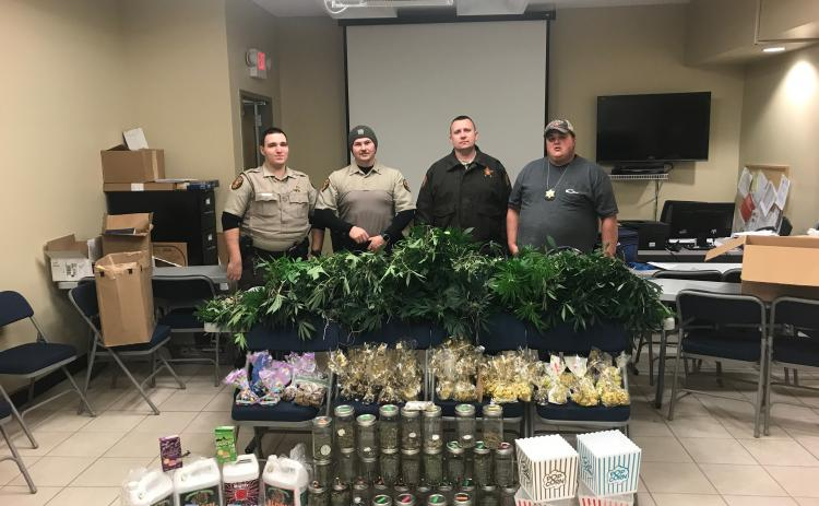Sunshot from file — Hart County Sheriff's deputies Luke Bennett, Michael Davis, Jared Tollinson and Capt. Kevin White pose for a photo with an array of marijuana plants and marijuana-related products allegedly being grown and manufactured at a house on Lanier Street in Hartwell.