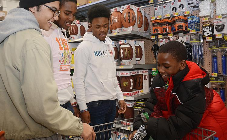 Sunshot by Michael Hall — Bishireon Smith tries on football gloves at Walmart on Dec. 12 with Hart County seniors Keyon Flowers, Kaimon Rucker and Tyler Rucker during this year's event.