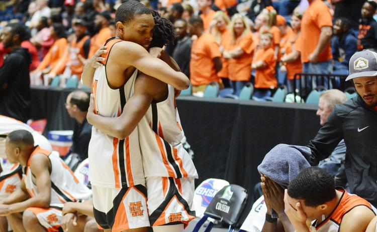 Sunshot from file — Hart County sophomore Shone Webb, left, consoles teammate, senior Elijah Robinson as time ticks down in the Bulldogs' state championship loss in March in Macon as other teammates sit on the bench with heads in hands.