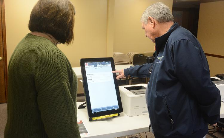 Hart County Board of Elections supervisor Robin Webb, left, and Paul Bishop, a poll worker, demonstrate how the new Dominion voting machines operate much like an iPad when casting votes.