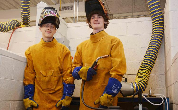 Sunshot by Michael Hall — Hart College and Career Academy students Zack Hart, left, and Austin Brown, right, pose for a photo in the welding lab at the school recently.  The pair were hired recently to work at Fabritex in Hartwell.