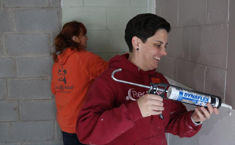 Sunshot by Grayson Williams — RedRover Outreach Manager Katie Campbell, right, and Bryna Donnelly, left, Director of GreaterGood.org's Rescue Rebuild program, caulk and paint a new indoor kennel area at the Northeast Georgia Council on Domestic Violence's shelter.