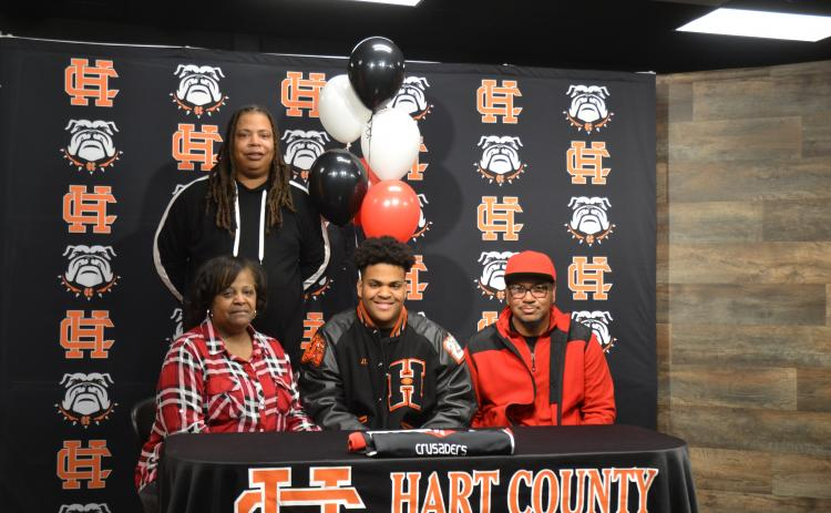 Sunshot by Drew Dotson - Hart County defensive lineman JT Hunt, center, poses for a photo after signing with his father Ronnie Hunt, right, brother Marco Hunt, standing, and mother Jennifer Hunt.