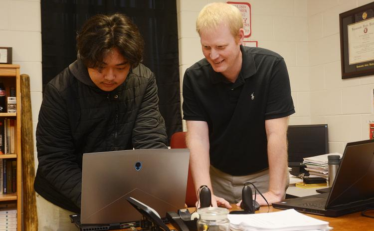 Sunshot by Michael Hall - Hart County High School's STAR student, Sean Pak, left, and STAR teacher, Rob Elliot, right, look over the coding of a video game last week they created along with the TSA video game competition team.