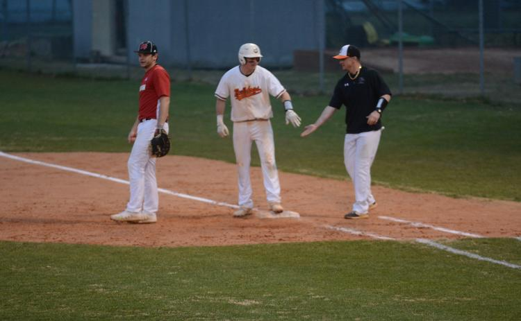 Luke Lee, left, is congratulated by coach Hunter Barton, at first base after Lee's line drive that drove in a run to take the lead against Morgan County on Monday at Saye Field.