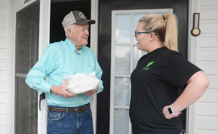 Sunshot by Michael Hall — Dan Powell, 90, left, accepts a free meal from Southern Hart Brewing Co. employee Emily Reynolds last Thursday in Hartwell.
