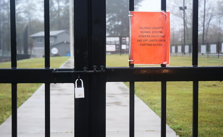 The gate at Saye Field at Hart County High School is locked with a note about the grounds being off limits.