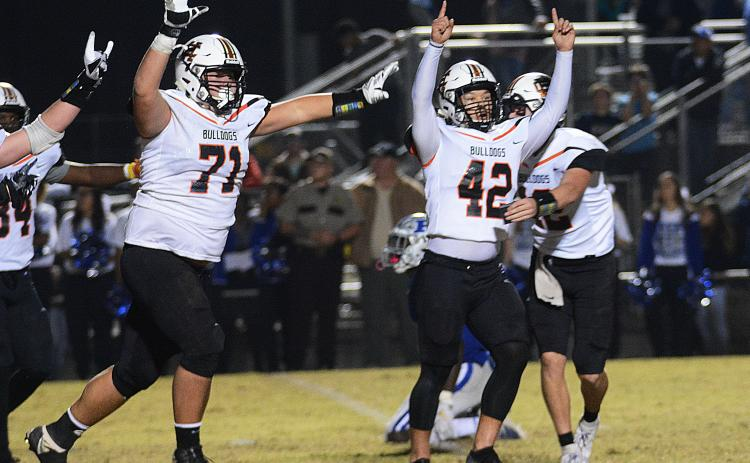 Sunshot by Michael Hall — Hart County kicker Tucker Kim, No. 42, raises his hands in victory along with Caden Hart, No. 71, while quarterback Luke Lee tackles Kim after Kim's game winning field goal on Nov. 22, 2019 in Blackshear over the Pierce County Bears.