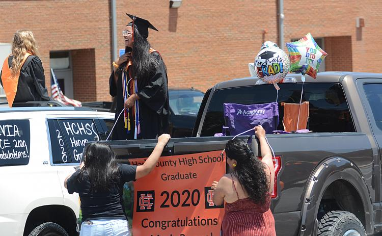 Sunshots by Michael Hall Maria Rangel talks with another graduate as her family helps her hang a banner from the back of a truck prior to the Parade of Graduates on May 23 in Hartwell.
