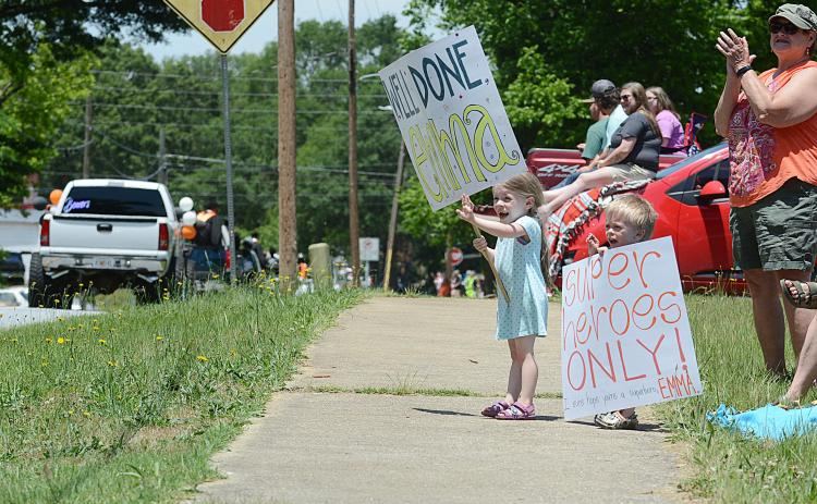 Violet Ayers, left, 6, and Jasper Ayers, 4, right, hold signs in support of their cousin Emma Ayers on Saturday, May 23, during the Parade of Graduates in Hartwell. — Sunshot by Michael Hall