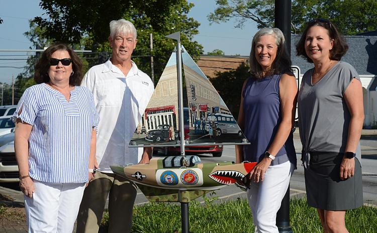 Sunshots by Michael Hall — From left to right, artist Debbie Gurley, Bo Howard, Tina Howard and artist Angela Short pose for a photo with the new sailboat installed Wednesday at Carolina and Howell streets to honor where service members boarded buses to go to World War II. The Howards spearheaded the fundraising for the project.