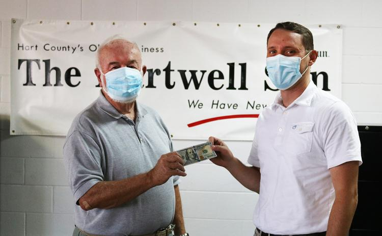 Sunshot by Grayson Williams — Photographer Bill Powell, left, accepts the $100 prize for winning the Summer Lake Living cover photo contest from The Hartwell Sun publisher Michael Hall.