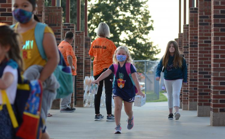 Sunshot by Michael Hall — Danica Kerr, middle, a first-grade student at Hartwell Elementary, runs to class after being dropped off at the school on Monday, Aug. 17 for the first day of the 2020-2021 academic year.